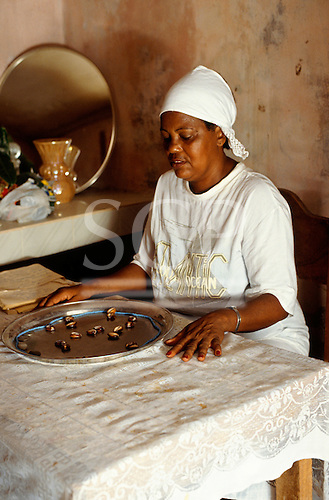Recife, Brazil. Candomble Priestess reading the Buzios (cowrie shells) to foretell the future.