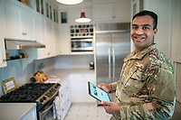 Happy young off duty US Army soldier at home in his kitchen, for sale as stock photography