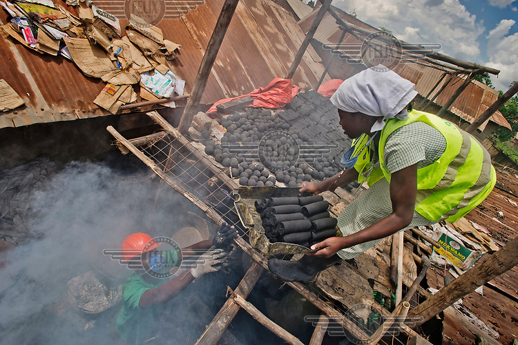 A member of the Lulana Communal Environmentalist's workshop passes a container of briquettes, made from recycled or waste cardboard and used for cooking fuel as an alternative to charcoal or wood, up to a colleague on a roof for drying.