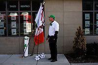 A man stands next to flags waiting for the start of the St. Patrick's Day Parade in South Boston, Massachusetts.