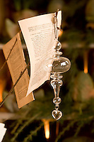 A glass bauble together with pages torn from a book hang from a branch used as a Christmas decoration