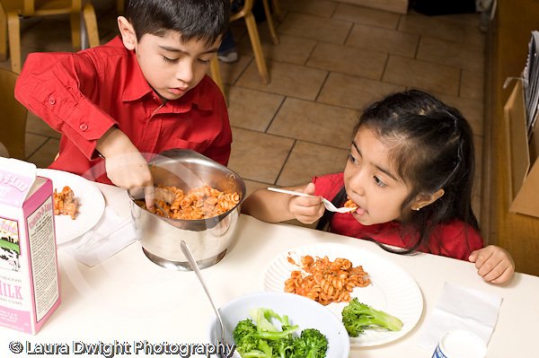 Headstart Preschool 3-5 year olds lunch time boy and girl eating hot lunch boy serving self vegetable broccoli girl eatng pasta with tomato sauce horizontal