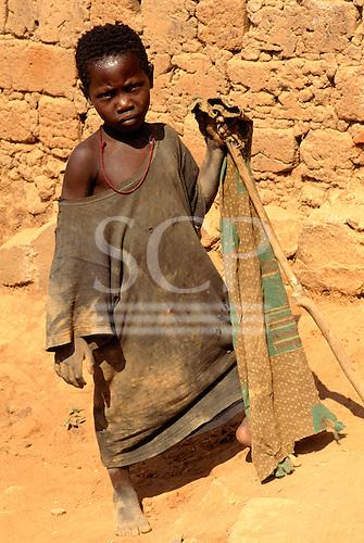 Kala, Tanzania. Girl in ragged clothes holding a stick; Lake Tanganyika.