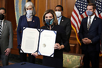 Speaker Nancy Pelosi (D-Calif.) holds H.R. 24, an article of impeachment against President Donald Trump, after an engrossment ceremony on Wednesday, January 13, 2021 at the U.S. Capitol.<br /> Credit: Greg Nash / Pool via CNP /MediaPunch