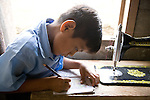A Mayan boy colors in a coloring book on the sewing table in his home in the Mayan community of San Miguel, Toledo, Belize