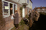 The Biddenden Charity Dole. Kent UK 1980s. Easter Monday.  Local OAP collect bread, cheese and tea from the window of the Old Workhouse Cottage.