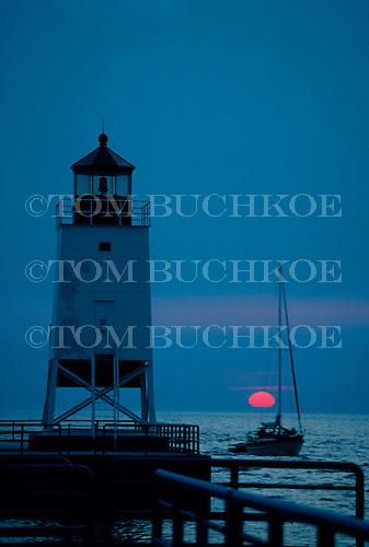Charlevoix Lighthouse, Charlevoix, Michigan, Lake Michigan with sailboat at sunset.