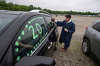 Graduate Sebastian Barajas of Bentonville  decorates his car Tuesday June 1, 2021 before the Haas Hall Academy 2021 graduation ceremony at the 112 Drive-In in Fayetteville. The school first hosted commencement ceremonies at the drive-in movie theater last year due to the covid-19 pandemic. The class had a total of 155 graduates from Haas Hall's four campuses: Bentonville, Fayetteville, Rogers and Springdale. Visit nwaonline.com/2100602Daily/ and nwadg.com/photo. (NWA Democrat-Gazette/J.T. Wampler)