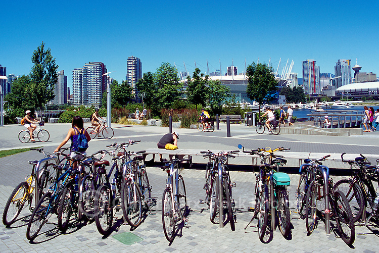 Vancouver, BC, British Columbia, Canada - Bicycles locked in Bike Stand at the Village on False Creek, BC Place Stadium and City of Vancouver on Horizon
