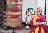 Bodhnath, Nepal.  Monk at Entrance to Buddhist Shrine Guarded by Mythical Snow Leopard, Prayer Wheel Spinning on Left.