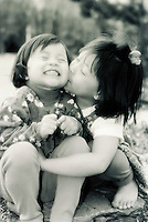 Chinese American sisters kissing