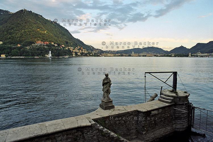 Una statuetta ad un approdo sul Lago di Como. Sullo sfondo: Como --- A statue on a dock at Lake Como. On the background: Como