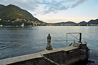 Una statuetta ad un approdo sul Lago di Como. Sullo sfondo: Como --- A statue on a dock at Lake Como. On the background: Como