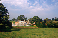 A country house with turrets and gothic windows is surrounded by protective copses of trees