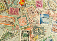 Assortment of Colorful Old Postage Stamps from Various Countries Around the World against a 1929 Map of the World<br />