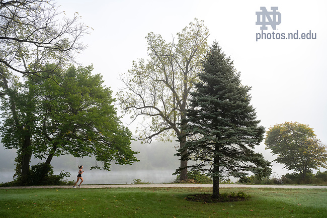 October 13, 2021; A student jogs along the trail of St. Mary's Lake as morning fog rolls in over campus. (Photo by Barbara Johnston/University of Notre Dame)