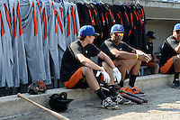 Aberdeen IronBirds Federico Castagnini (6) and Oswill Lartiguez (40) sit on the dugout step in front of the players pants and jerseys hanging from the railing before a game against the Williamsport Crosscutters on August 4, 2014 at Bowman Field in Williamsport, Pennsylvania.  Aberdeen defeated Williamsport 6-3.  (Mike Janes/Four Seam Images)