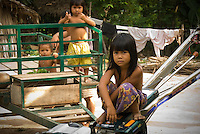 Young children in a small village around 30 km from Siem Reap cautiously watch as visitors stroll through their village. Life in the small villages is very different to life in the city of Siem Reap despite it's proximity. The average family in Cambodia lives on less than a dollar US per day -- and even lower in rural areas such as this one.