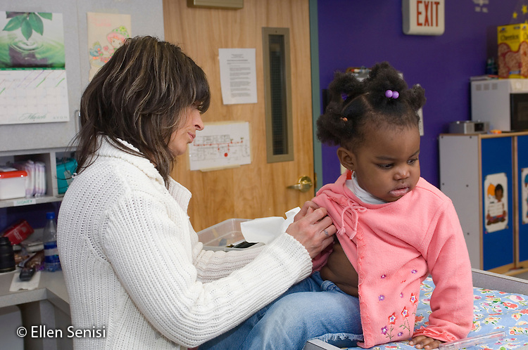 MR / Schenectady, NY.Schenectady Day Nursery / private non-profit daycare center / Toddler class.Teacher is taking sick child's (girl, 2, African-American) temperature with an underam thermometer..MR: Ada6, Eti2.© Ellen B. Senisi