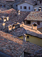 Brick chimneys and tile roofs of homes in the Umbrian hilltown of Montone Italy