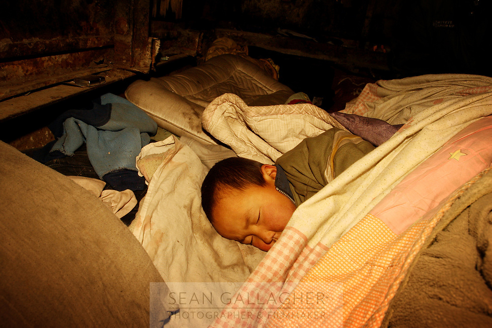 MONGOLIA. Ulaan Baatar. 6-year year old Huyga, sleeping soundly, alone in the darkness whilst his parents and grandfather go out and search the street for bottles. Leaving their child is an obvious risk, especially as rumours abound about homeless children being abducted from the street in recent years. As the global financial crisis grips Asia, Mongolia is feeling the implications first hand as the country suffers from rising inflation pushing the price of food and fuel ever upwards. For the country's homeless, who live in sewers and abandoned garages in the capital and already face extreme discrimination and are denied access to basic health and social care, their lives are hanging in the balance. 2008