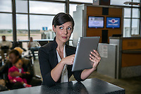 Happy business woman using tablet computer while sitting in airport gate departure lounge at the Austin International Airport. Horizontal shot.