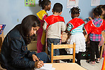 Education preschool 4-5 year olds female SEIT writing notes and observations in classroom as group of children in smocks play at water table