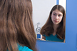 13 year old teenage girl in bathroom self care looking at self in mirror horizontal