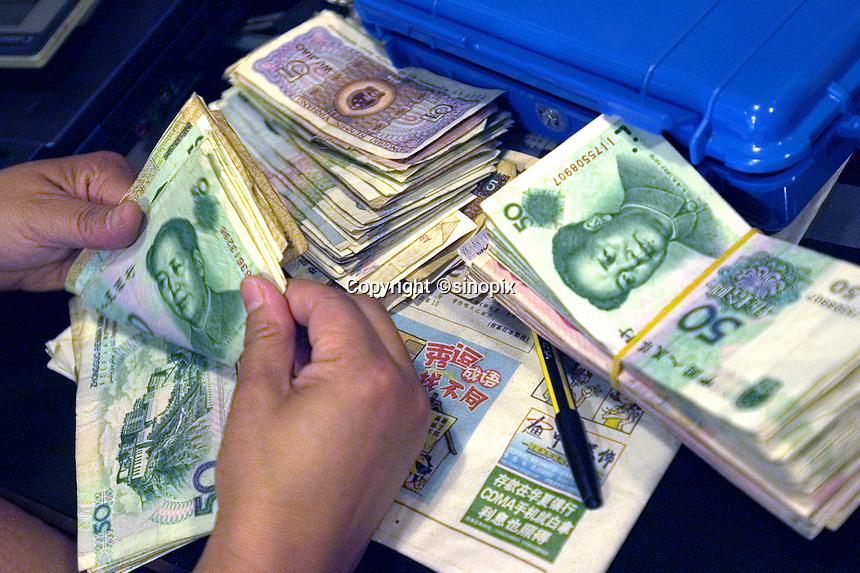 A woman counts Renminbi (RMB) in Beijing, China..