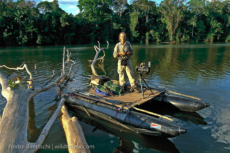 Wildlife photographer André Baertschi on a catamaran in wait for giant otters, lowland tropical rainforest along an oxbow lake in Manu National Park, Madre de Dios, Peru.