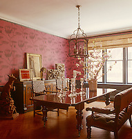 In the dining room, lined with a dramatic pink wallpaper with outsize floral motifs, the table is English with a billiard bench on one side and woven-leather Arts & Crafts chairs on the other