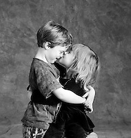 Young boy and girl playfully hugging.