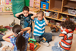 Education preschool 4-5 year olds group holding hands over ears to protect from imaginary explosion