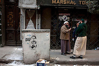 Men talk to one another taking a break from protesting on a side street off Tahrir Square where the main protest in occuring. Continued anti-government protests take place in Cairo calling for President Mubarak to stand down. After dissolving the government, Mubarak still refuses to step down from power. On a stone boulder in the street, someone has drawn devil horns onto graffiti of Mubarak.
