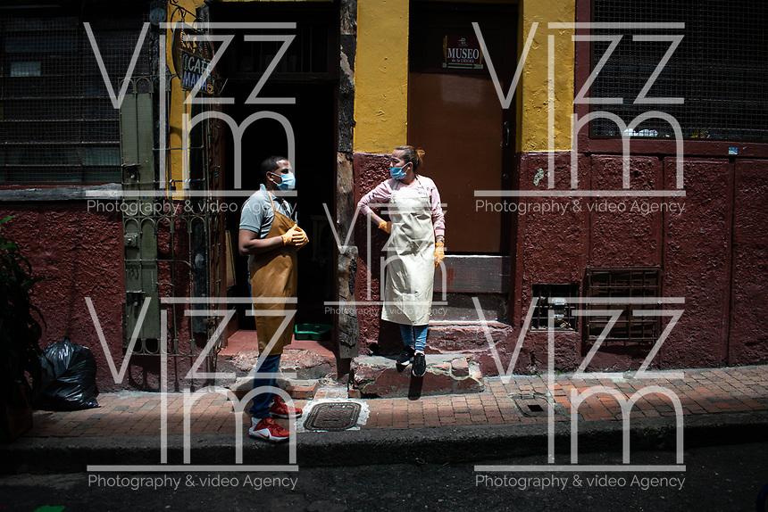 """BOGOTA - COLOMBIA, 05-09-2020: Propietarios de una café esperan por clientes durante el primer día del piloto de apertura de restaurantes y cafés al aire libre, denominado """"Bogotá a Cielo Abierto"""", en el Chorro de Quevedo en el centro de Bogotá que ahora tiene sus calles pintadas con formas geométricas en pintura neón y cuenta con mesas, distribuidas estratégicamente para mantener el distanciamiento físico al finalizar la cuarentena total en el territorio colombiano causada por la pandemia  del Coronavirus, COVID-19. / Café owners wait for customers during the first day of the pilot for the opening of restaurants and outdoor cafes, called """"Bogotá a Cielo Abierto"""", in Chorro de Quevedo in the center of Bogotá, which now has its streets painted with geometric shapes in neon paint and has tables, strategically distributed to maintain physical distancing at the end of the total quarantine in the Colombian territory caused by the Coronavirus pandemic, COVID-19. Photo: VizzorImage / Johan Rugeles / Cont"""