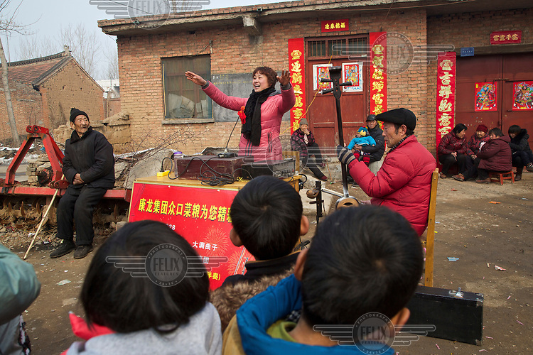 Storyteller Zhao Tao performs at a village soon after she appeared at the Ma Jie folk festival. <br /> <br /> For centuries farmers in Henan have gathered during Chinese New Year in the region's wheat fields to listen to bards singing and recounting old tales. <br /> <br /> Now storytellers come from all over China to attend the annual festival where large crowds gather to watch the best performers, many of whom will be booked to perform in nearby villages following the festival.