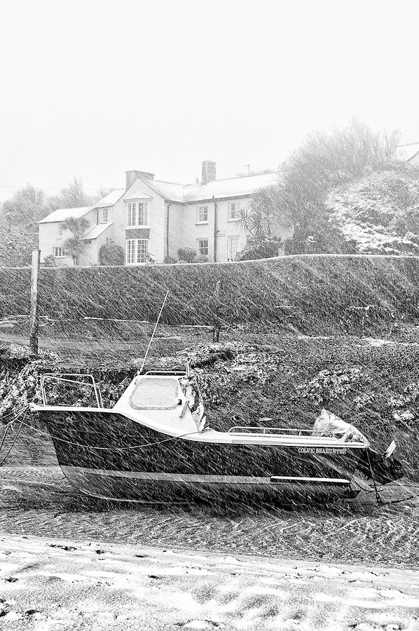 Efford Cottage lies at the end of the Bude Canal and on the side of Summerleaze Beach. Here a snowstorm is blowing across the cottage and a boat on the sands in front of it. These are fairly rare conditions in a Cornish beach resort.