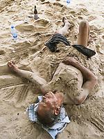 Thailand. Trat province. Sand beach near the village of Ban Bang Bao on Ko Chang island. A drunk man sleeps on the sand beach. Plastic bottle of water. 12.04.09 © 2009 Didier Ruef..