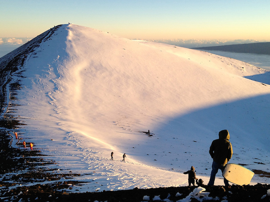 Visitors explore the snow-covered summit of Mauna Kea on the Big Island of Hawaii. Mauna Kea is 13,796ft high but from from the bottom of the ocean, is the tallest mountain in the world at 33,500ft.  Due to its high altitude, dry environment and isolated geographical location, Mauna Kea's summit is one of the best sites in the world for astronomical observation. Since the creation of an access road in 1964, thirteen telescopes funded by eleven countries have been constructed at the summit.