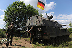 "German soldiers including Captain Maximilian Beenisch (at left) beside a howitzer at the Drawsko Pomorskie Training Area in Poland on June 10, 2015.  NATO is engaged in a multilateral training exercise ""Saber Strike,"" the first time Poland has hosted such war games, involving the militaries of Canada, Denmark, Germany, Poland, and the United States."