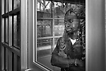 A black man looking through a glass door at a train station