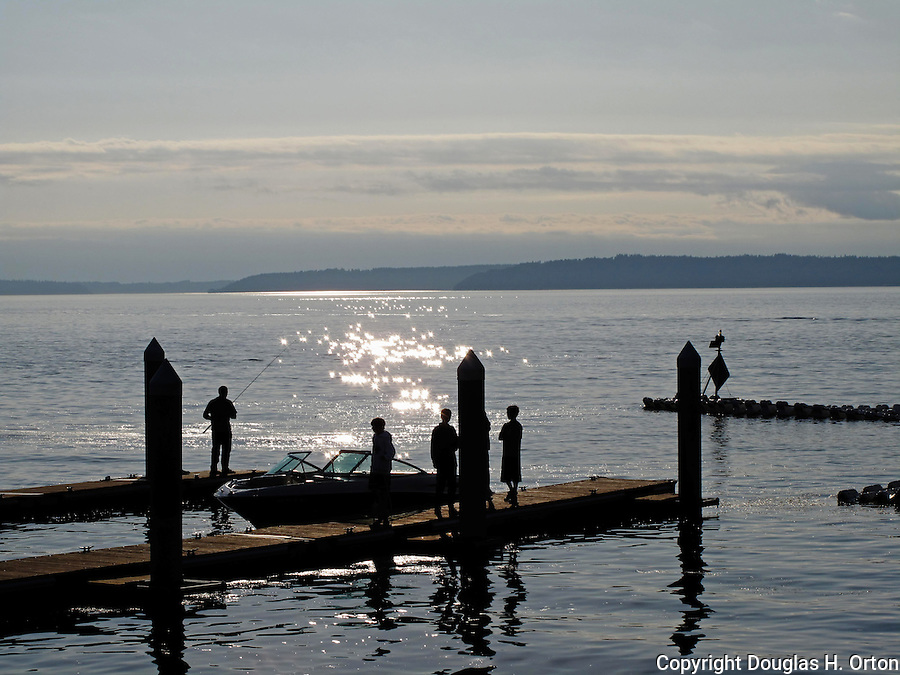 Boaters wait at Redondo Beachboat ramp, south of Seattle, Washington, on a misty Puget Sound evening. Near fishing pier and Highline Community College MAST center.  Dash Point and Browns Point on Puget Sound are in the distance.   View from Washington SR509.  Vashon Island, Maury Island and city of Tacoma in background.