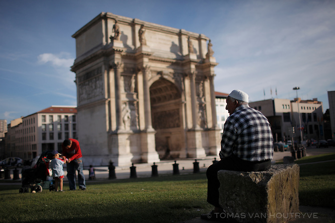 A man wearing a muslim skullcap sits in a park overlooking the Porte d'Aix Arc de Triomphe in Marseille on 11 July 2009.