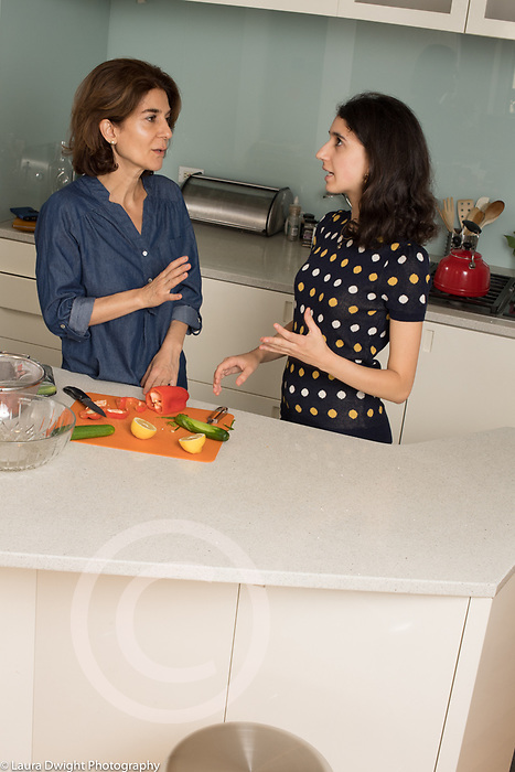 18 year old teenage girl at home, food preparation, in kitchen with mother preparing salad ingredients, discussion