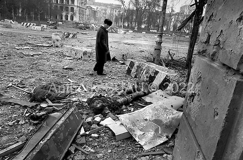 Grozny, Chechyna.1995.A well dressed man glaces at the corpse of a Chechen fighter still lying in the streets of central Grozny.