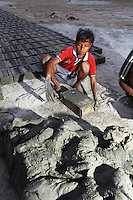 A child works in a brick factory, in the Malancha district of eastern Kolkata. As their parents work nearby, children often play in the area, exposing them to harmful materials and waste produced in the industrial process. India. November, 2013