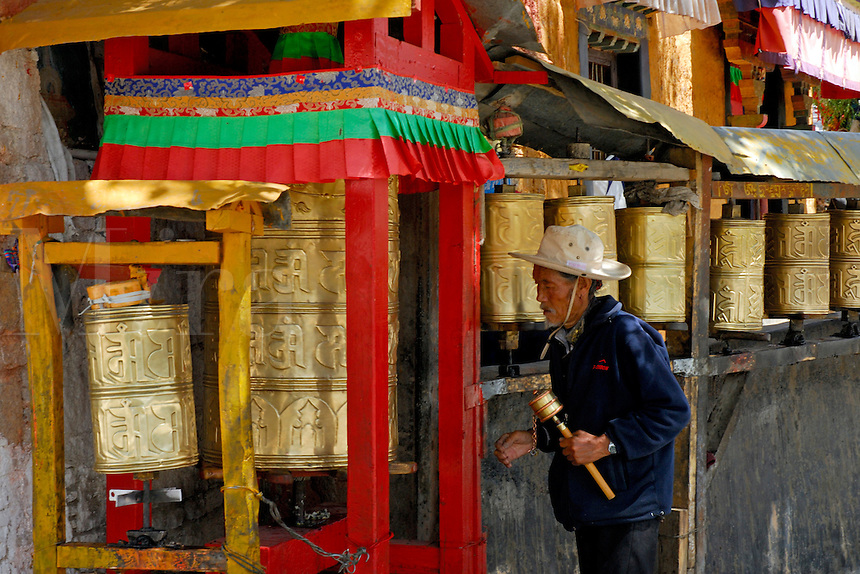 Tibetan Buddhist pilgrim spins prayer wheels outside a small prayer hall on the northeast side of the Potala Palace, while completing the sacred pilgrim circuit, or Tsekor, around the outer walls of the Palace, Lhasa, Tibet, China.