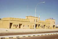 Kuwait March 1972.  Old-style Houses, probably dating from the 1950s.  Water storage tanks on rooftops; individual room air conditioning units in windows.  TV antenna.  Minaret in background.  Divided roadway. AN ADDITIONAL 100 HISTORIC IMAGES OF KUWAIT MADE BETWEEN 1966-1972 ARE AVAILABLE.  LET US KNOW WHAT YOU NEED.