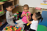 Education Preschool Head Start Early  Learn 2s Program group of three children 2 boys and a girl playing with plastic building toys in class