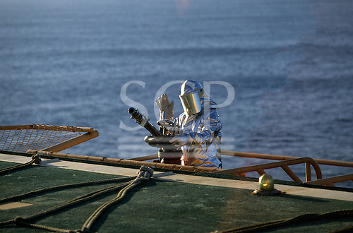 Rio de Janeiro, Brazil. Oil rig worker in silver fireproof suit and helmet with visor and water cannon fire hose.